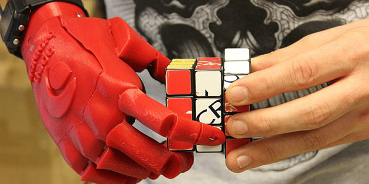 Image of a prosthetic hand solving a Rubik's cube