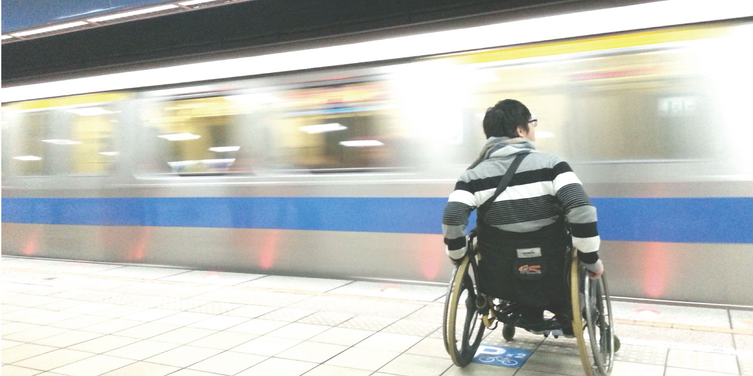 Image of a man in a wheelchair waiting for a train