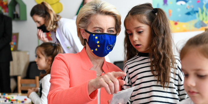 Commission President von der Lezen wearing a mask with an EU flag on it, explaining something to a child.